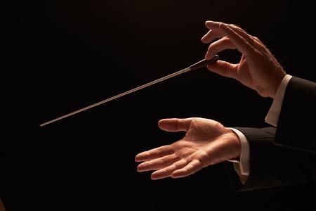 orquesta clasica: Director de orquesta dirigiendo una orquesta aislada sobre fondo negro Foto de archivo