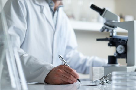 Scientist making notes conducting research looking through microscope selective focus