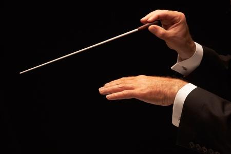orquesta: Director de orquesta dirigiendo una orquesta aislada sobre fondo negro Foto de archivo