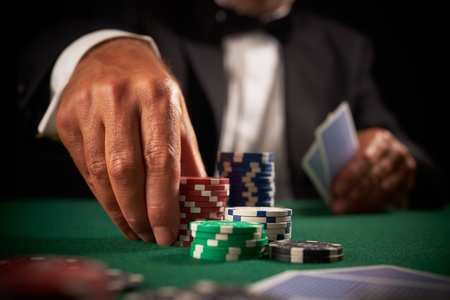 cartas de poker: Card player apostar fichas de casinos en enfoque selectivo fondo fieltro verde