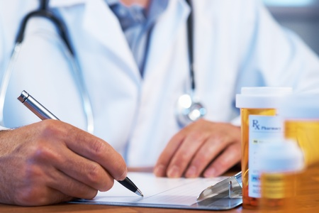 pharmacist: Doctor writing  RX prescription drug bottle selective focus