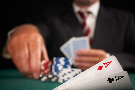pair of aces and poker player gambling casino chips on green felt background selective focus photo
