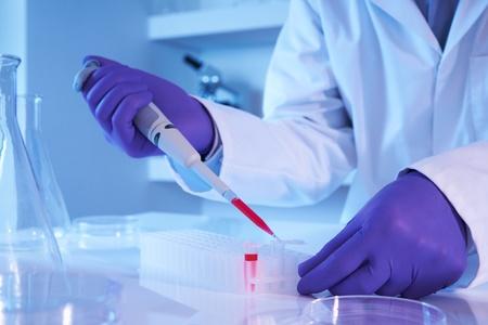 genetica: Scienziato con pipetta a fuoco selettiva di laboratorio