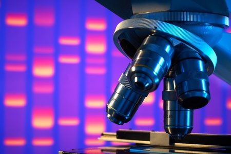 genetic information: Close up of laboratory microscope with DNA gel image background  Stock Photo