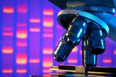 drug discovery: Primo piano del microscopio da laboratorio con immagine di sfondo gel DNA
