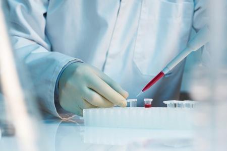 genetic information: close up of scientist using pipette in laboratory selective focus