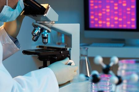 cromosoma: Científico en el microscopio con la imagen de fondo en el ADN