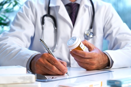 Doctor writing out RX prescription selective focus