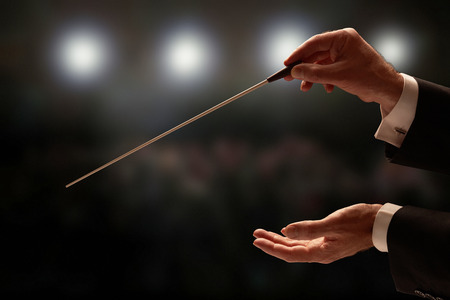 Conductor conducting an orchestra with audience in background