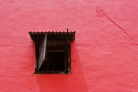 A window on a red wall