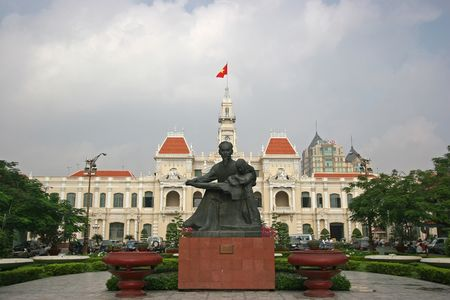 Peoples Committee building in Ho Chi Minh City, Vietnam, with Ho Chi Minh statue in front
