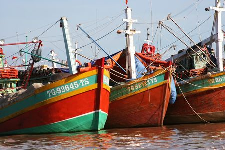 A row of colorful fishing boats berthed at the port in the Mekong Delta, Vietnam Stock Photo