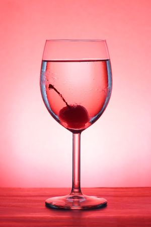 Red Cherry in a goblet over red background photo