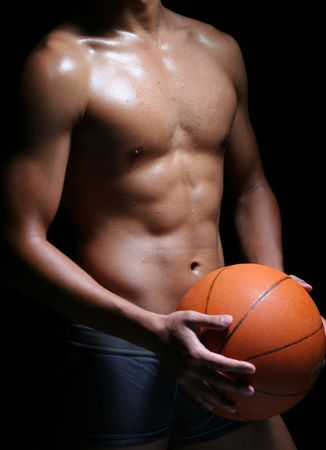 manhood: hunky asian basketball player in trunks with a ball Stock Photo