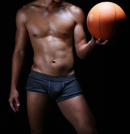 front view of a hunky asian basketball player with a ball in his left hand