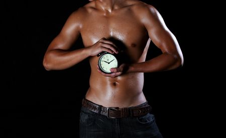 a hunky asian young man holding an alarm clock in his hands Stock Photo - 3885594