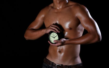 A hunky young asian man holding a ticking clock in his hands, Stock Photo - 4046125