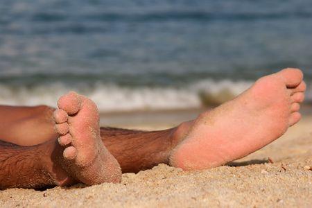 hairy legs: a pair of sandy feet on a sandy beach  Stock Photo