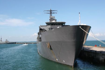 A navy war ship parking at the berth in a jetty