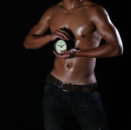 hunky asian young man holding a ticking clock Stock Photo - 5930262