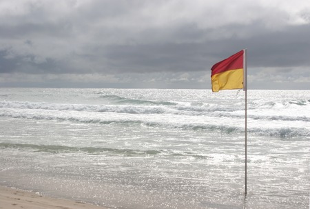 imminent: Swim flag flying lonely at an empty Surfers Paradise beach amid an impending storm at the sea, Gold Coast, Australia