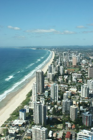 surfers: Long stretching golden sandy beach and modern skyscrapers at the beach front of Surfers Paradise in Gold Coast, Queensland, Australia