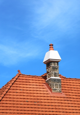 atop: Chimney atop a roof with red tiles Stock Photo