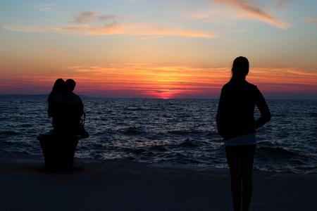 ragazza innamorata: Silhouette di un womanl solo guardando un suo ragazzo barare su di lei con un'altra donna sul tramonto sul mare, la loro relazione sta affondando come il sole al tramonto Archivio Fotografico