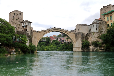 drizzling rain: The old bridge that crosses  river Neretva and connects the two parts of the city of Mostar, in Bosnia and Herzegovina, in a gloomy and rainy day