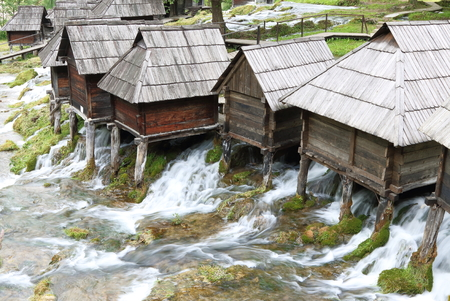 watermills: Wooden huts housing the traditional watermills at Pliva Lake in Jajce, Bosnia Stock Photo