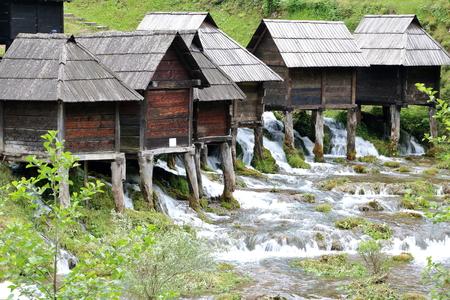 watermills: Wooden huts housing the traditional watermills at Pliva Lake, Jajce, Bosnia and Herzegovina Stock Photo