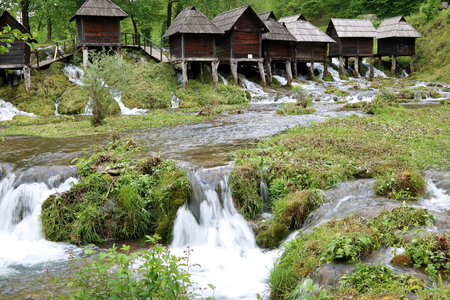 watermills: Wooden huts housing the traditional watermills at Pliva Lake, Jajce, Bosnia and Herzegovina Stock Photo