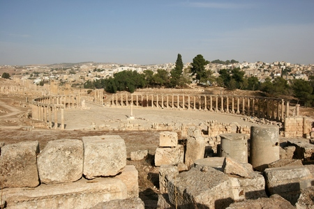 Oval Plaza of Jerash Roman ruins with Jerash modern town in the background, Jordan Stock Photo