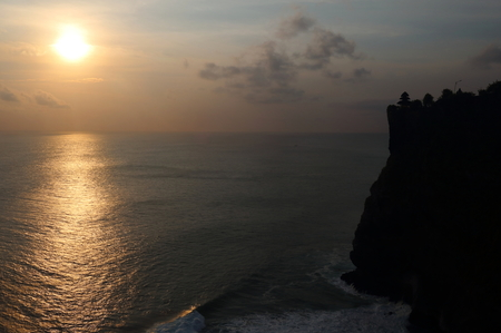 Dusk at Uluwatu in Bali, with the silhouette of famous Uluwatu Temple on the right Stock Photo