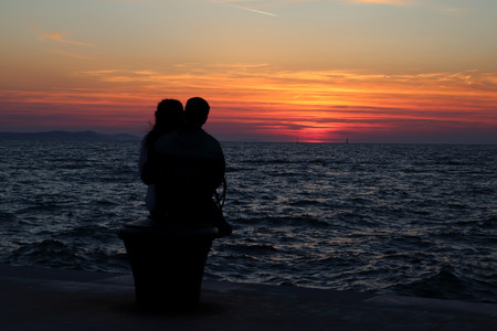 A loving couple sitting together to watch the worlds most beautiful sunset at Zadar, Croatia