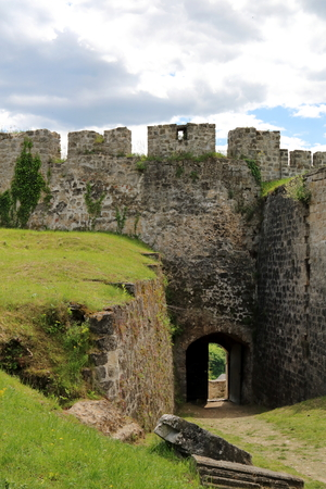 The half opened gate of the abandoned Jajce Fortress in Bosnia and Herzegovina, with the defense wall and passage way, in a sunny day with dark storm clouds