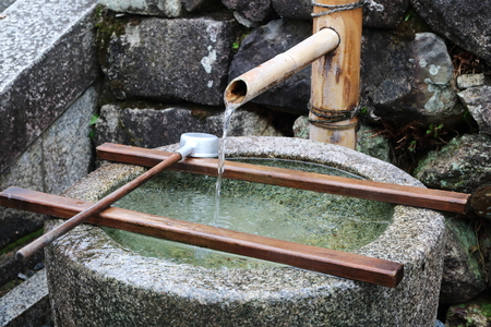 Japanese purificaition fountain with running water from a bamboo trunk, into a stone basin