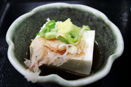 Tofu side dish decorated with ginger, spring onion and cuttle fish gross in Kyoto