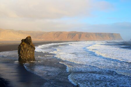 Famous Kirkjufjara black sand beach at sunset in the Southern Coast of Iceland, where the waves have be treacherous Stok Fotoğraf
