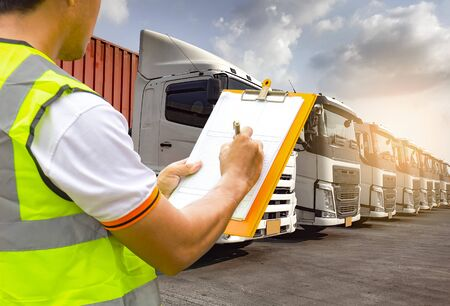 Worker holding clipboard to control and manage the loading of trucks. Road freight industry service cargo logistics and transport