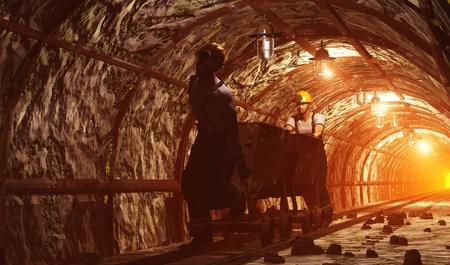 Trabajadores empujando el carrito de la mina.