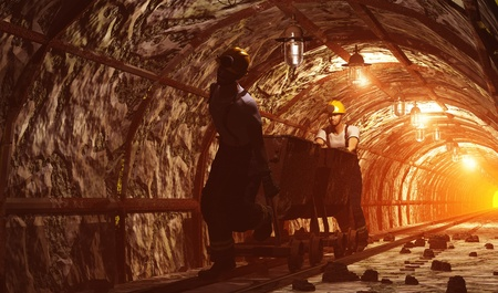 COAL MINER: Workers pushing the cart in the mine. Stock Photo
