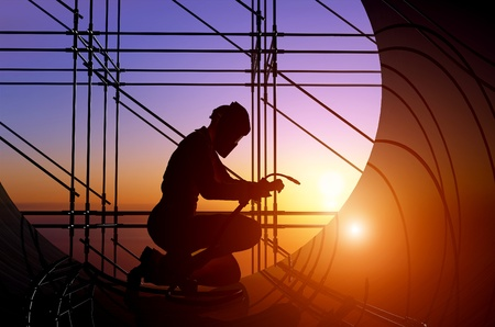 A silhouette of a worker-welder. Stock Photo