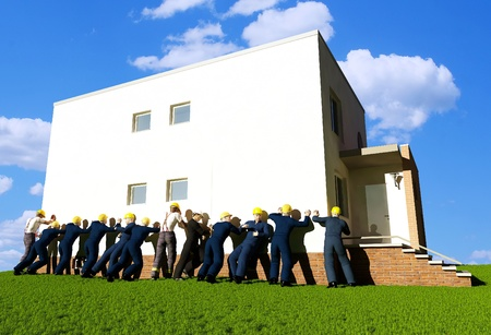 Group  builders are pushing the home on green grass. photo
