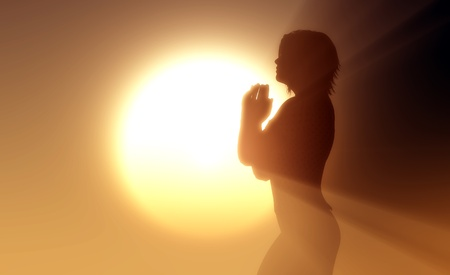 jesus praying: A girl prays in the rays of the sun. Stock Photo