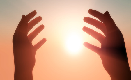 catholic symbol: Silhouettes of hands in the sunshine.