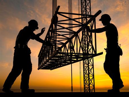 De groep werknemers werken op een bouwplaats.