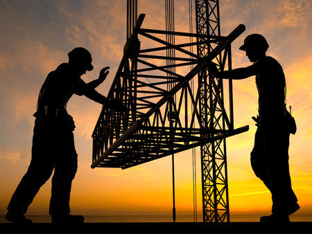 building structures: The group of workers working at a construction site.