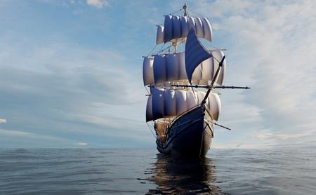 Barca a vela d'epoca in mare al tramonto.