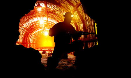 hard: Silhouettes of worker in the mine.